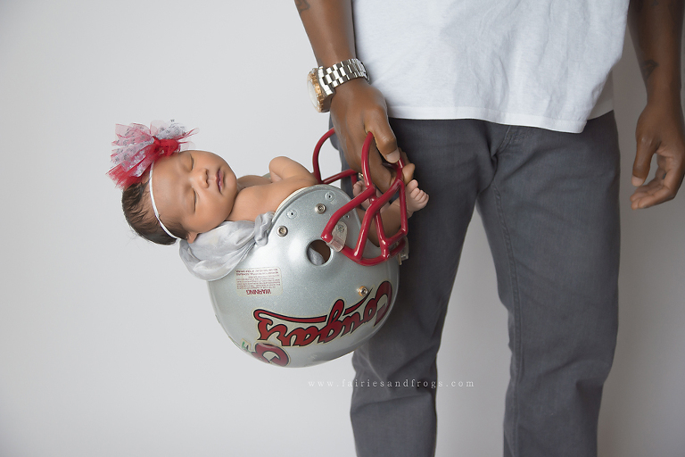Newborn photo session with baby alseep in football