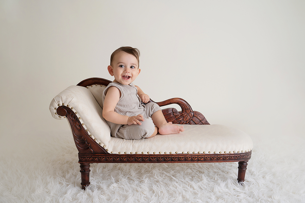 First birthday photo with a baby posing on a recliner