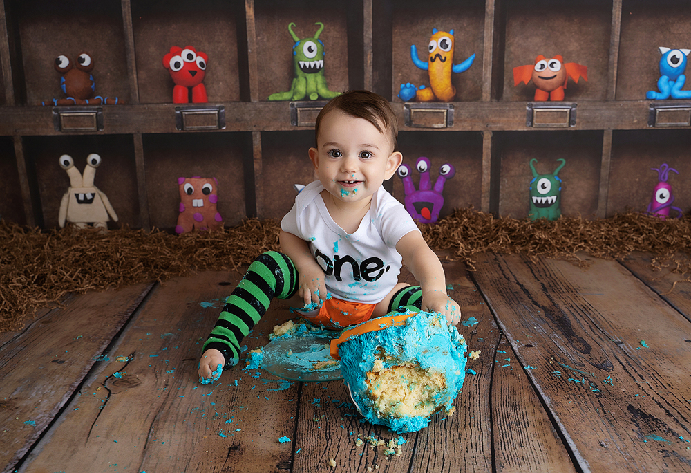 A one-year-old smiles at the camera with a messy blue cake in front of him for a monster cake smash photoshoot