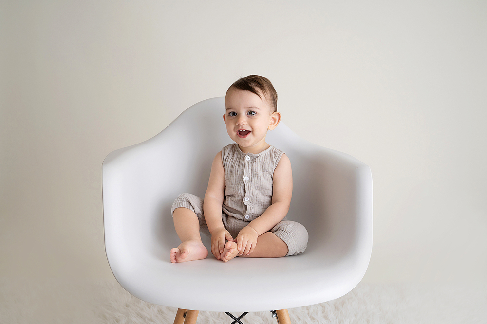 Minimal baby photography on a white chair with a white background