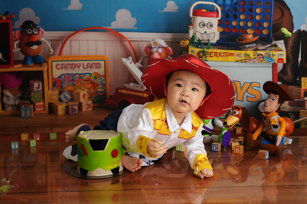 Toy Story photoshoot with a baby girl in a Jessie costume and cake to smash