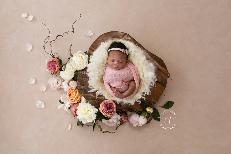 When to schedule newborn photos  - newborn photo in a fur blanket surrounded by pastel flowers