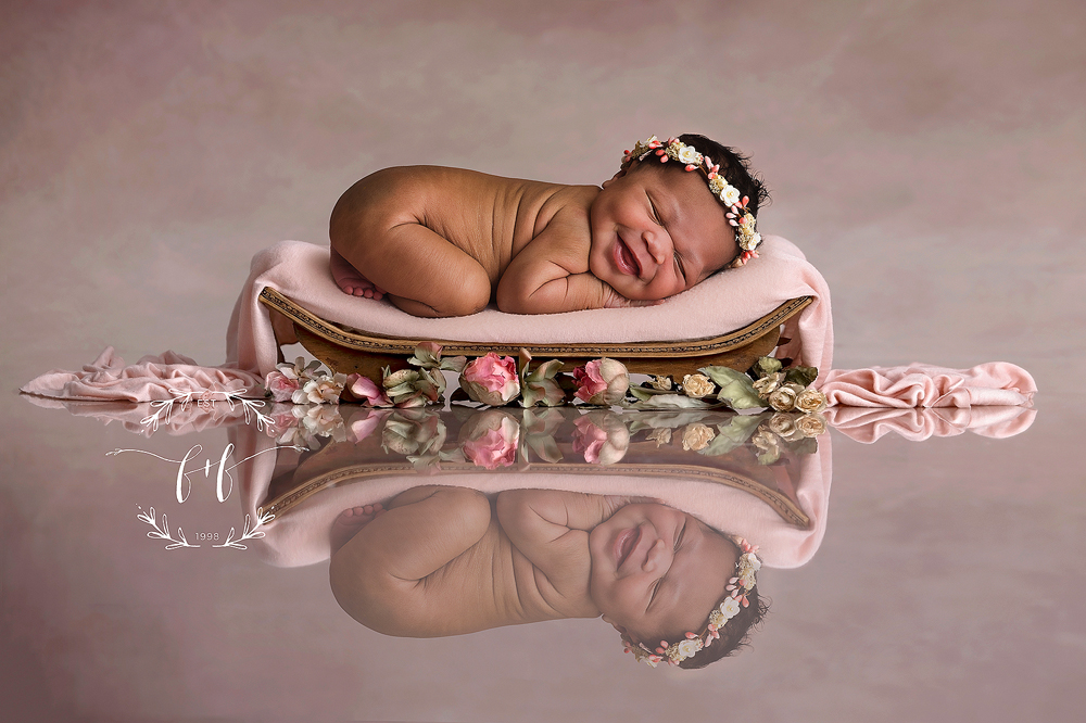 Smiley newborn sleeps on a pink blanket with her reflection showing underneath