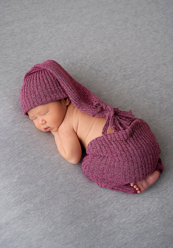 A newborn sleeps in a maroon nightcap and gown