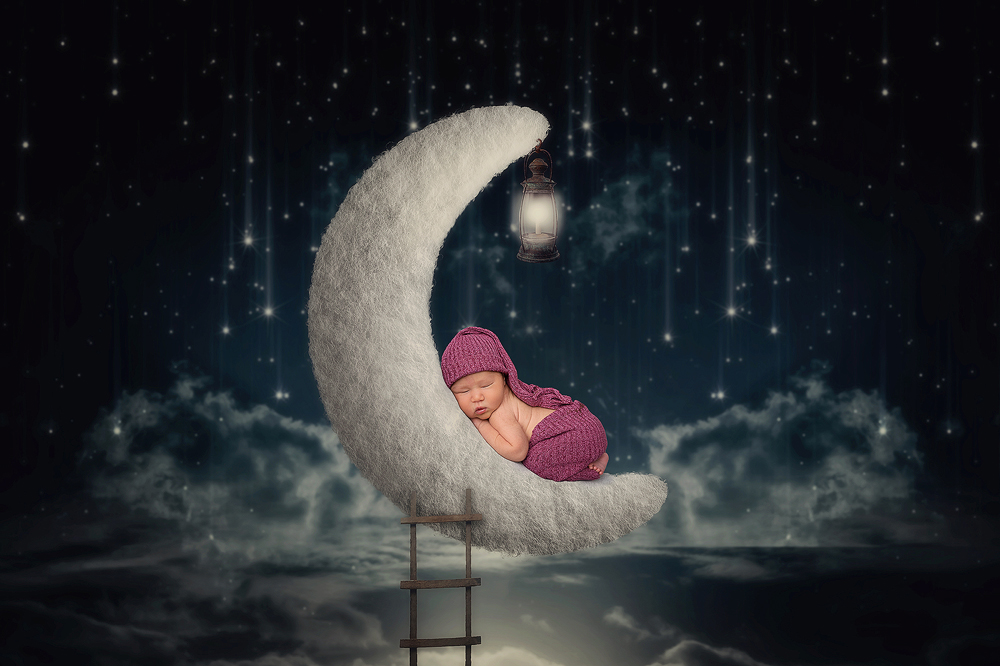 Newborn moon photography with a baby sleeping on a crescent moon