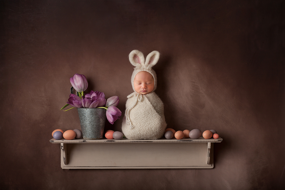 Easter bunny newborn photo with a sleeping baby on a shelf with pink and purple eggs