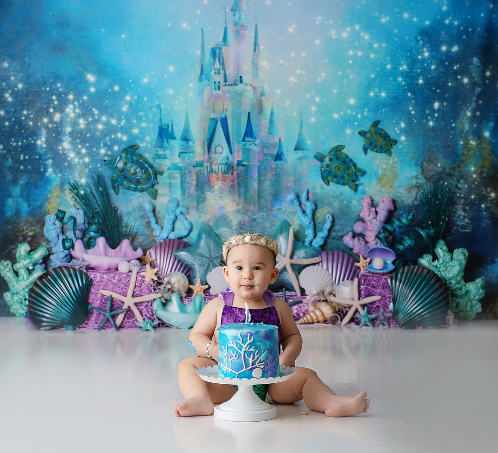 A baby dressed in a Little Mermaid outfit with a blue cake and under the sea backdrop