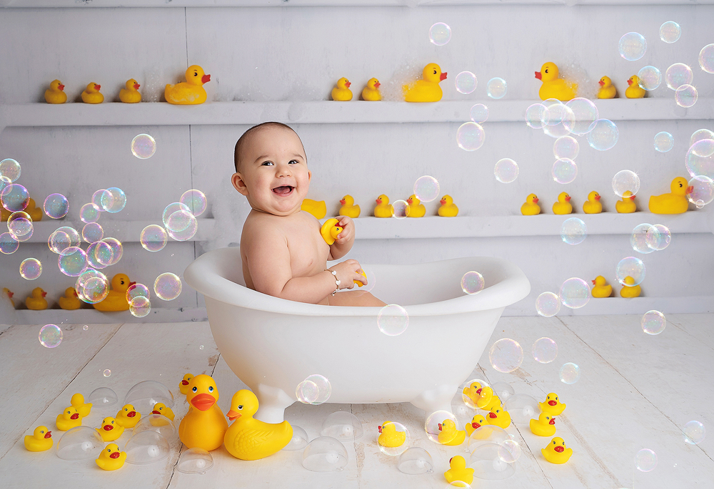 Baby smiles in a bath tub with yellow rubber ducks and lots of bubbles