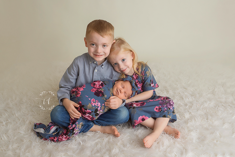 Two young children holding their new baby sister on a fur blanket with floral dresses